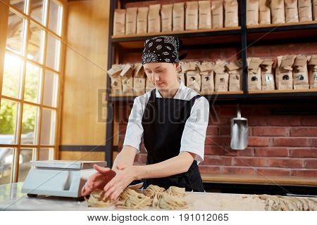 Horizontal indoors shot of female cook forming taglatellepasta in a kitchen of restaurant. Woman forming taglatellein cafe