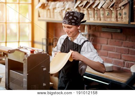Cheerful female cook rolling a dough through pasta making machine on restaurant kitchen. Woman preparing knead for pasta. Cheerful woman working with pasta machine. Making pasta