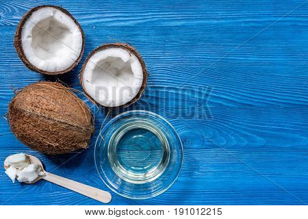 coconut water in glass to drink and fresh coconut on blue wooden desk background top view mock up