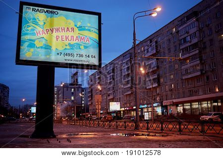 MOSCOW, RUSSIA - FEB 28, 2017: Street traffic on highway near billboard with inscription External Advertising on winter evening.