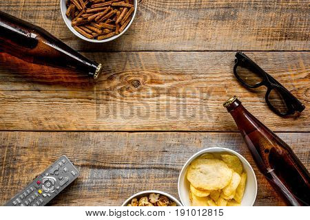 home party with TV watching, snacks, pop corn, chips and bread crumbs and beer on wooden background top view mock up
