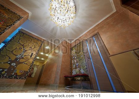 MOSCOW, RUSSIA - MAR 1, 2017: Interior of hallway in flat decorated with tiles and mosaics by pictures G.Klimt, low angle view.