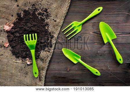 rake, trowel, ground for gardening on wooden desk background top view