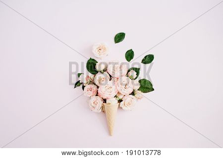 Waffle cone with pink bombastic roses bouquet on pale pastel pink background. Flat lay top view