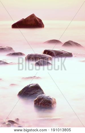Romantic Morning At Sea. Big Boulders Sticking Out From Smooth Wavy Sea. Long Exposure