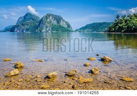 Stony beach during low tide in front of huge rocks in Background, El Nido, Palawan, Philippines.