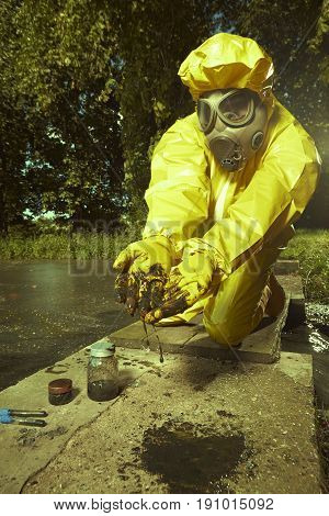 Man in chemical protective suit collecting samples of bad water contamination