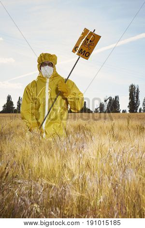 Man in protective suit protesting on field with genetically modified cereals