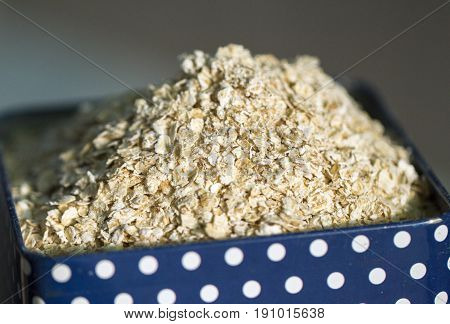 Oatmeal in metallic can. Oat cereal in polka dot container. Cozy kitchen detail photo. Healthy breakfast with oat. Nutritious meal for morning. Active lifestyle eating. Dry oats pile. Porridge cooking