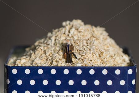 Oat cereal in metallic can and senior traveler figurine. Old person diet. Health care concept image. Aged man traveling over cereal mountain. Healthy breakfast ingredient and toy. Tiny person in oat