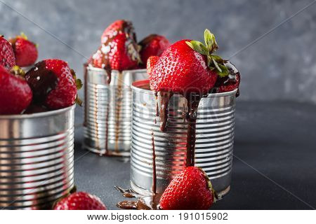 Fresh strawberry on gray background . Dessert with strawberries and chocolate caramel. Strawberries in the iron pot. Copyspace.