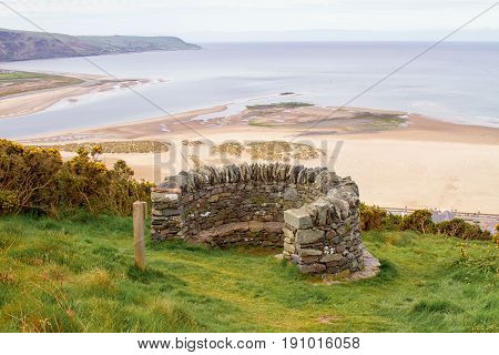 Landscape featuring the old fort stone look out above Barmouth beach Gwynedd. A beautiful Welsh coastal landscape