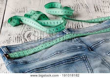 Blue Jeans And Measuring Tape In Waistband And In Body On Wood Background