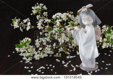 ceramic figurine in front of cherry blossoms close-up