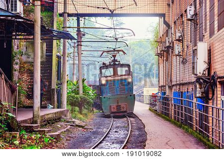 Electric narrow-gauge locomotive with the freight train moves through Yuejin town. Jiayang Mining Region. Sichuan province. China.