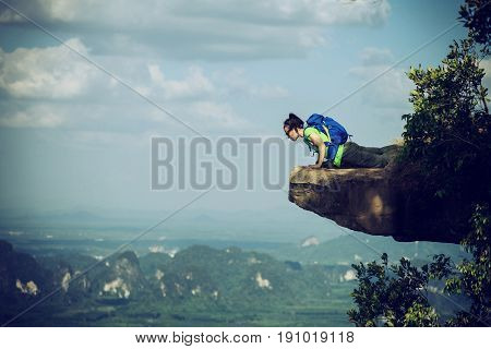brave woman hiker lying on mountain cliff looking down