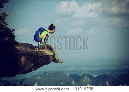 successful woman hiker sit on mountain top