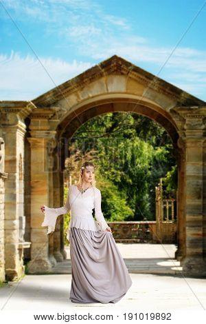 female high elf holding her skirt while walking on garden path