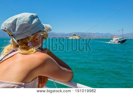 Caucasian female on boat looking to Fortaleza de Bourtzi, symbol of Nafplio, famous seaside town of Peloponnese in Greece, Europe. Woman boat trip enjoying the sea. Summer travel vacation concept.