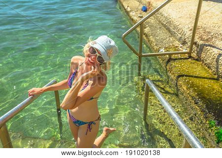 Happy tourist bikini woman talking on smart phone outdoors. Woman enjoying in travel holidays lifestyle Natural swimming pool in Nafplio, Peloponnese, Greece, Europe.Summer, travel and leisure concept