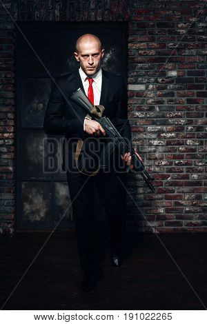 Assassin in suit and red tie holding machine gun