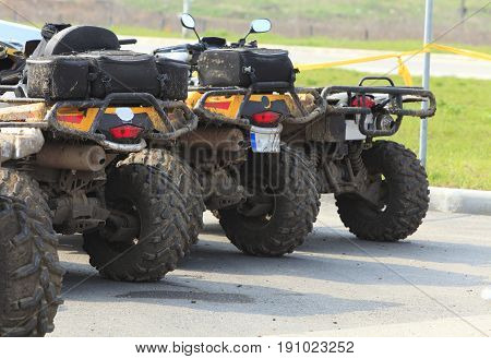 Low angle veiw of a row of dirty ATVs.