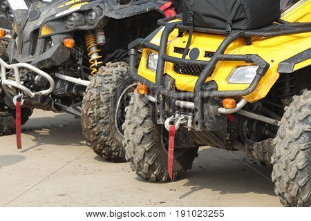 Low angle veiw of the front part of a row of ATVs.