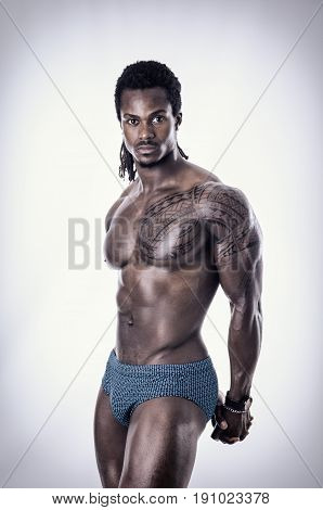 African American bodybuilder man, naked muscular torso, wearing bathing suit, isolated on white background