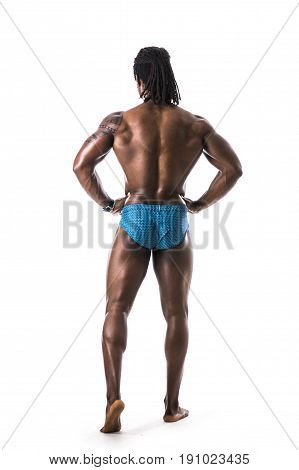 Muscular young black male bodybuilder posing, full length, seen from back, isolated on white background, wearing only underwear