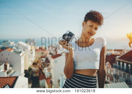 Serious attractive afro american female journalist with retro film photo camera young curly Brazilian girl holding vintage camera with Lisbon central district and Tagus river in defocused background
