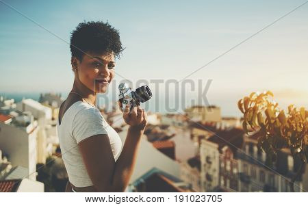 Curly young Brazilian lady half turned towards camera and smiling while standing on high observation point in Lisbon city and holding vintage film camera with copy space for logo message or advert