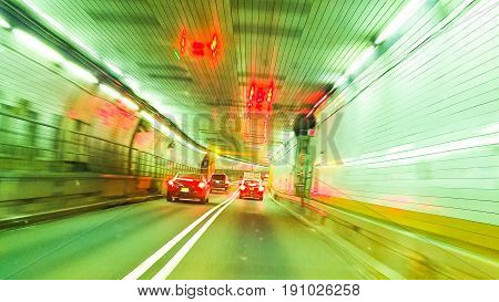 Cars driving in an underground driving tunnel. Green color filter.