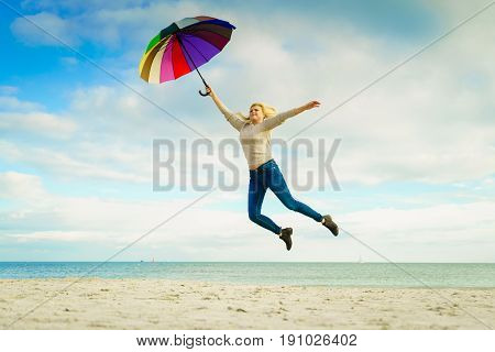 Happiness enjoying weather feeling great concept. Woman jumping with colorful umbrella on beach near sea sunny day and clear blue sky