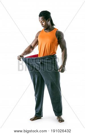 Black male bodybuilder has lost weight, wearing large pants and stretching them to see his progress