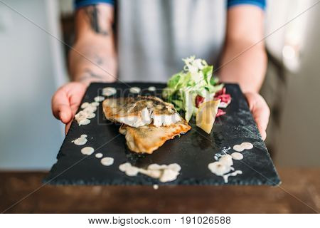 Male hands hold dish of fried fish fillet