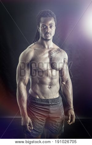 African American bodybuilder man, naked muscular torso, wearing pants only, against black background in studio shot