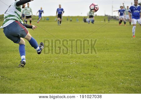 Claddagh Galway Ireland june 2017 Man executing a cross from a free kick in the free public soccer field as part of the Interfirm cup.