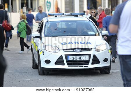 Shop Street Galway Ireland june 2017 Garda card driving down the pedestrian walk street.