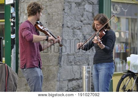 Shop Street Galway Ireland june 2017 Duo of violinist in the street.