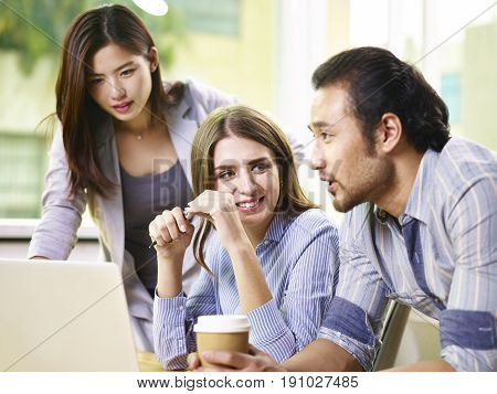 a team of asian and caucasian businesspeople working together in office.