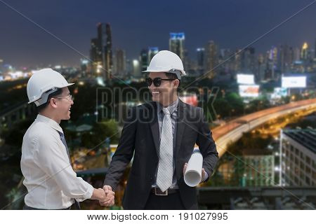 Asian Businessman Shake Hand With Engineer Architect Professional Wearing Safety Helmet And Holding