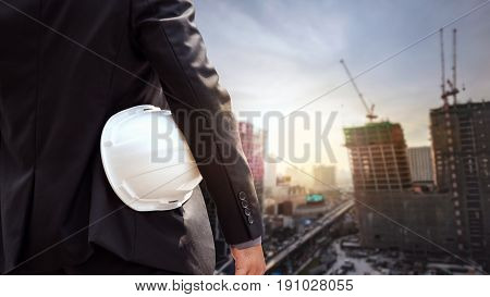 White Helmet Of Engineer Architect Holding By Businessman In Suit And Building Construction Site Bac