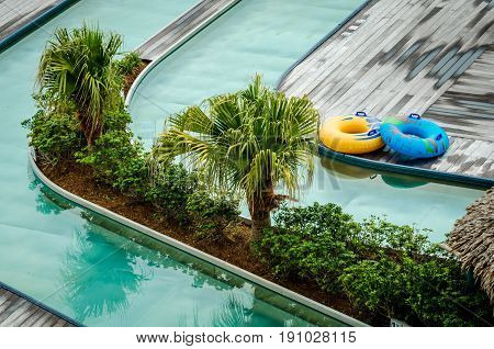 Tourist travel destination location for relaxation and fun.  Lazy river pool with tropical palm trees, deck and swim tubes.