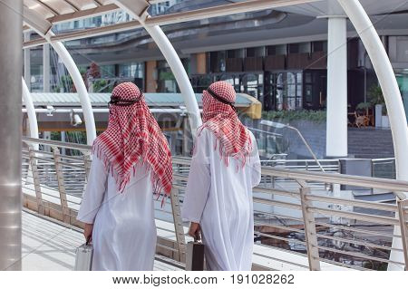 Two Arabian Businessman With Briefcase And Walk Together Around Modern City, Back View