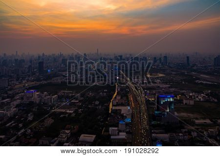 Aerial view of Bangkok city and traffic expressway with skyline at dusk twilight and fog or mist in bangkok cityscape