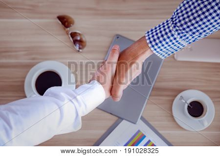 Hand Shake Business, Top View Of Two Men Shaking Hands Business And Wooden Table And Coffee Cup As B