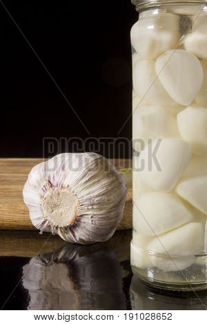 Marinated and fresh garlic with a grater on a dark background