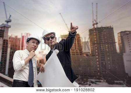 Asian Businessman Looking And Point To Finger Away And Engineer Architect Hold Construction Industri
