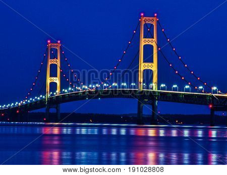 Mackinaw Bridge At Night. The Mackinac Bridge lights reflecting in the waters of Mackinaw Straits. It is the third longest suspension bridge in the USA and is located on Interstate 75 in Michigan.