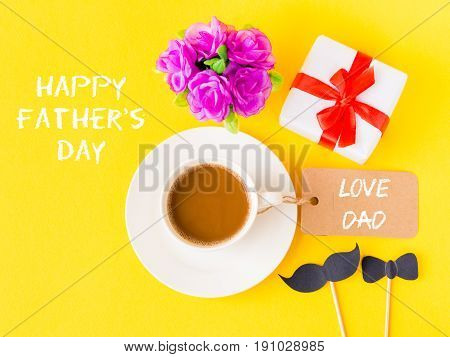 Father's day concept. Happy Father's Day and LOVE DAD message with pink flower coffee cup white gift and black Mustache on yellow background